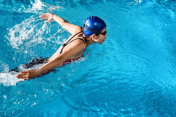 """os nadadores nadam """"borboleta"""" à beira da piscina à noite. - comodidades para lazer - fotografias e filmes do acervo"""