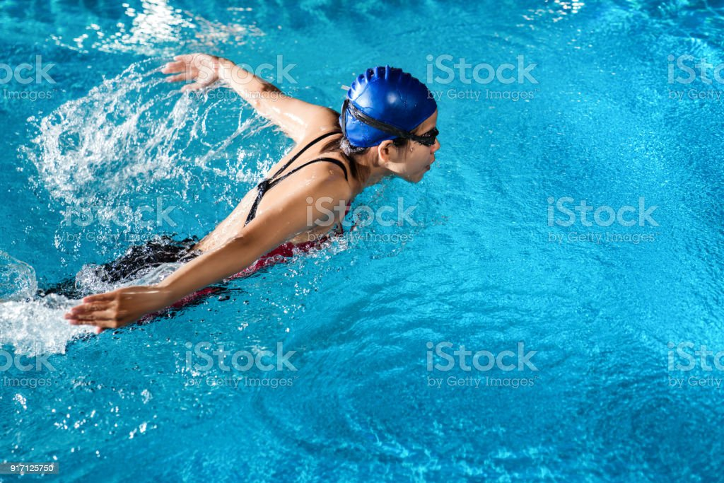 Nageurs nagent «papillon» près de la piscine pendant la nuit. - Photo