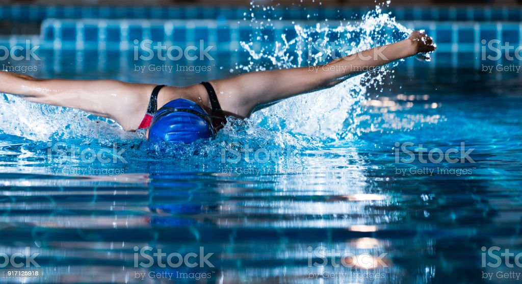 Swimmers are swimming 'butterfly' poolside at night. stock photo