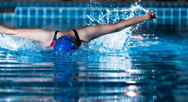 """swimmers are swimming """"butterfly"""" poolside at night. - competition group stock photos and pictures"""