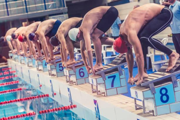 les nageurs accroupi sur à partir bloc prêt à sauter - starting block photos et images de collection