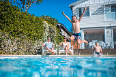 Family having fun in the backyard. Kids are swimming.