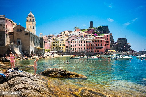 Cinque Terre, Italy - June 21, 2017: Tourists in swimsuits frolic in the sun in the turquoise colored water in the picturesque harbor of Vernazza village, a medieval seaside town with cramped  pastel-colored houses with   UNESCO site status.