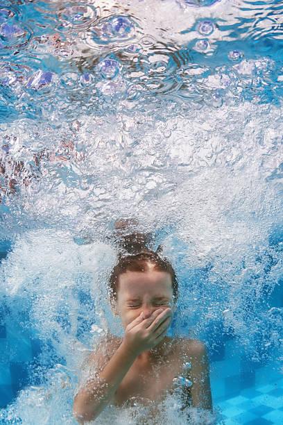 kind jumps unterwasser schwimmen im blauen pool mit kaskaden - splash fotos stock-fotos und bilder