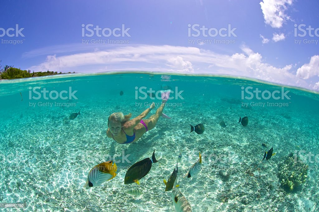 Swimming girl in tropical lagoon with fish and sky stock photo