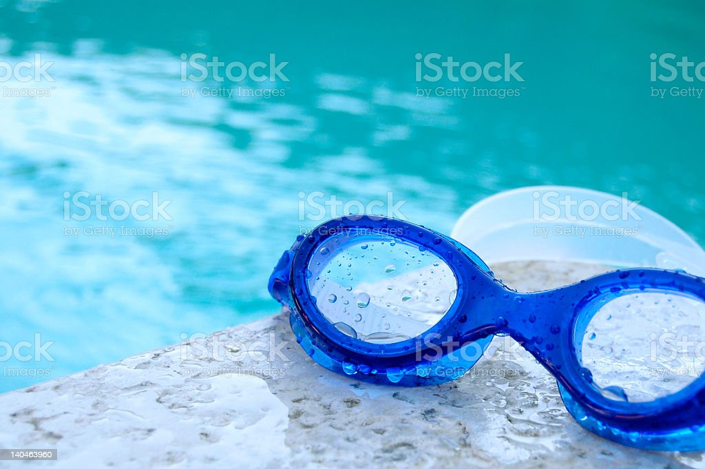 Swimming goggles sitting at the edge of a pool stock photo