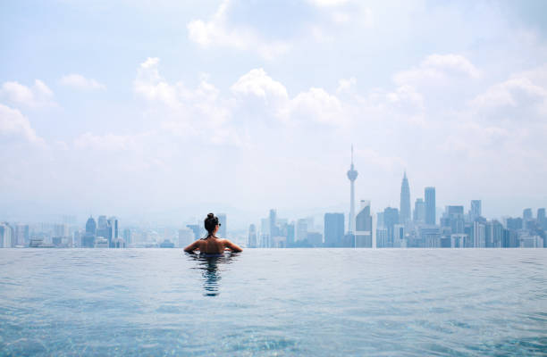 Swimming in the pool with a view Young brunette woman relaxing in the pool, swimming on top of the building in Kuala Lumpur, Malaysia. She is having a moment to relax after work in the busy city of Kuala Lumpur, Malaysia. infinity pool stock pictures, royalty-free photos & images