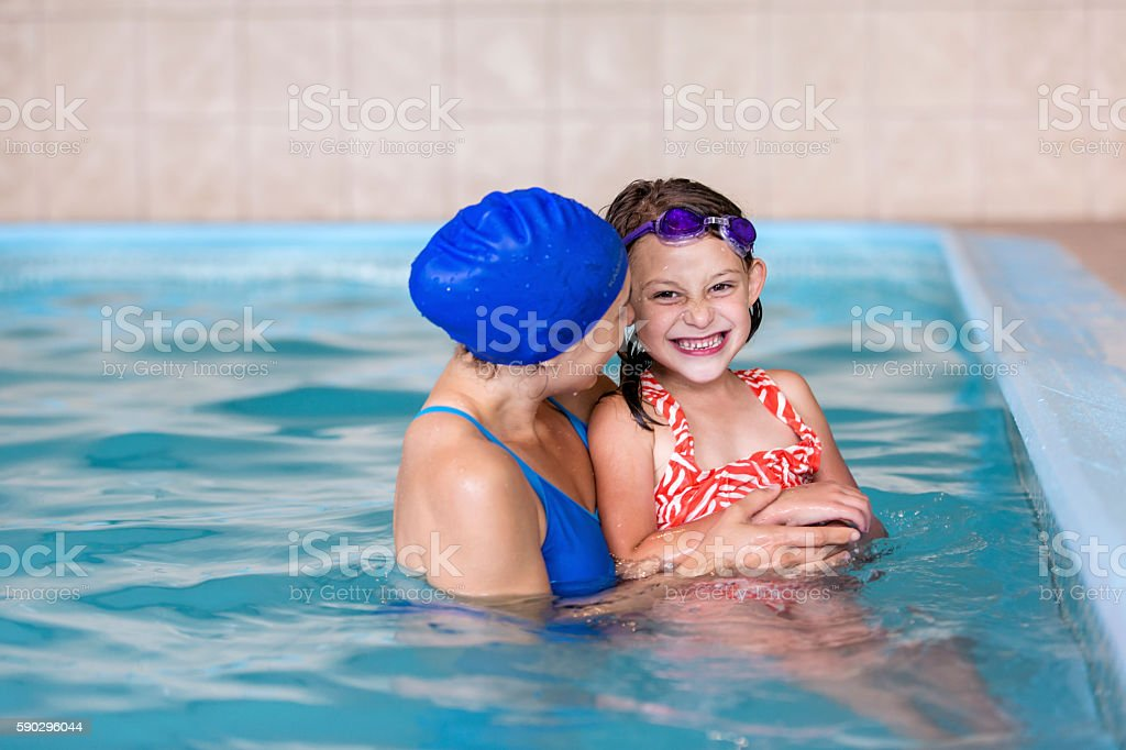 Swimming instructor laughing and smiling with a young girl royaltyfri bildbanksbilder