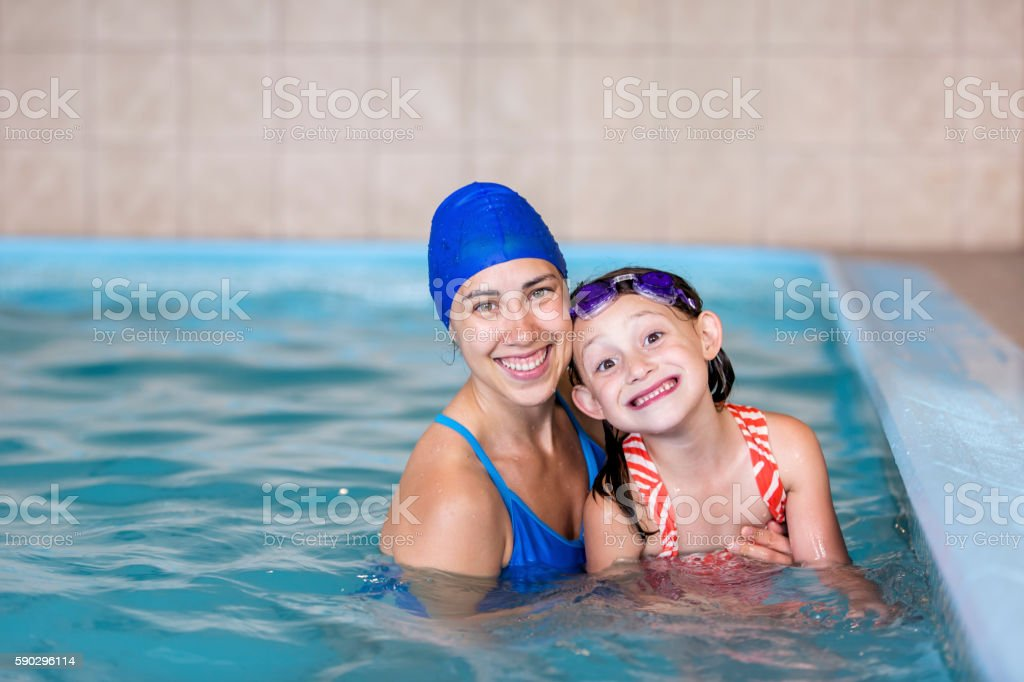 Swimming instructor smiling with a young girl in the pool royaltyfri bildbanksbilder