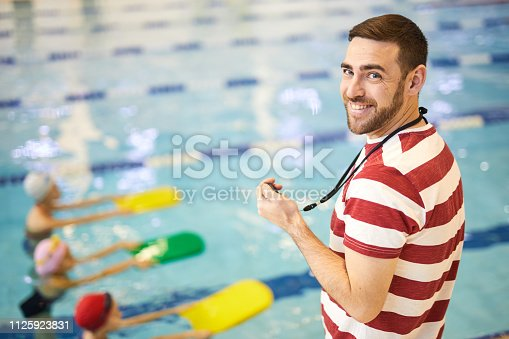 Portrait of smiling young swimming instructor training his group in the swimming pool