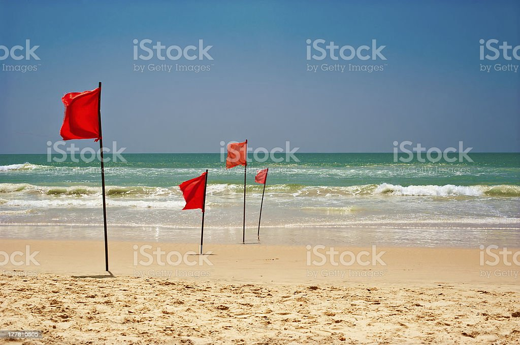 Swimming is dangerous in ocean waves. Red warning flag flapping stock photo