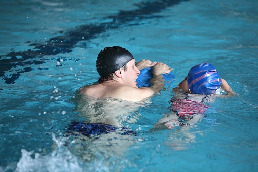 istock swimming lesson child practicing flutter kick with trainer 513393118