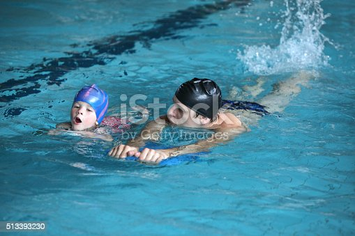 istock swimming lesson child practicing flutter kick with trainer 513393230