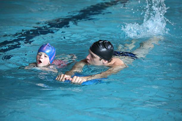 schwimmunterricht kind üben flatterärmeln und kick mit trainer - genderblend stock-fotos und bilder