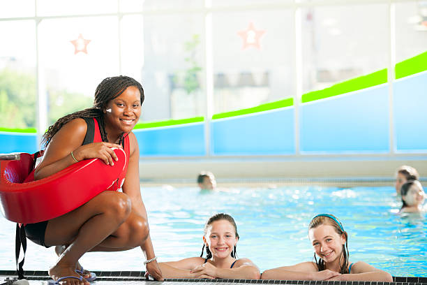 Swimming Lessons A group of children at a swimming pool. lifeguard stock pictures, royalty-free photos & images