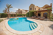 Luxury villa show home in tropical summer holiday resort with swimming pool bar and sun chairs