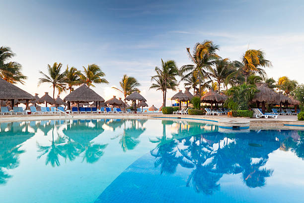 swimming pool at sunrise in mexico - playa del carmen stock photos and pictures