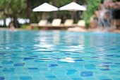 Swimming pool, Blue spa swimming pool with clean water, beach bed and beach umbrellas background