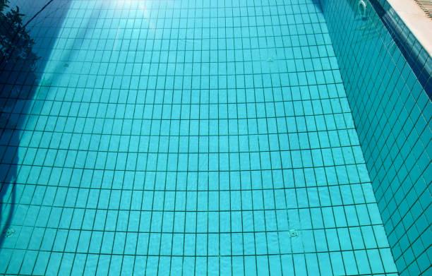 Ondulação do cáusticos inferior da piscina e fluxo com fundo das ondas. Superfície da piscina azul, fundo da água na piscina. Luz azul clara ondulações da água da associação com reflexões do sol. - foto de acervo
