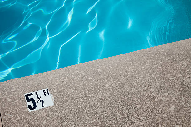 Swimming Pool Deck with Depth Marker; Shimmering Blue Water 5-1/2 feet depth marker at pool terryfic3d stock pictures, royalty-free photos & images
