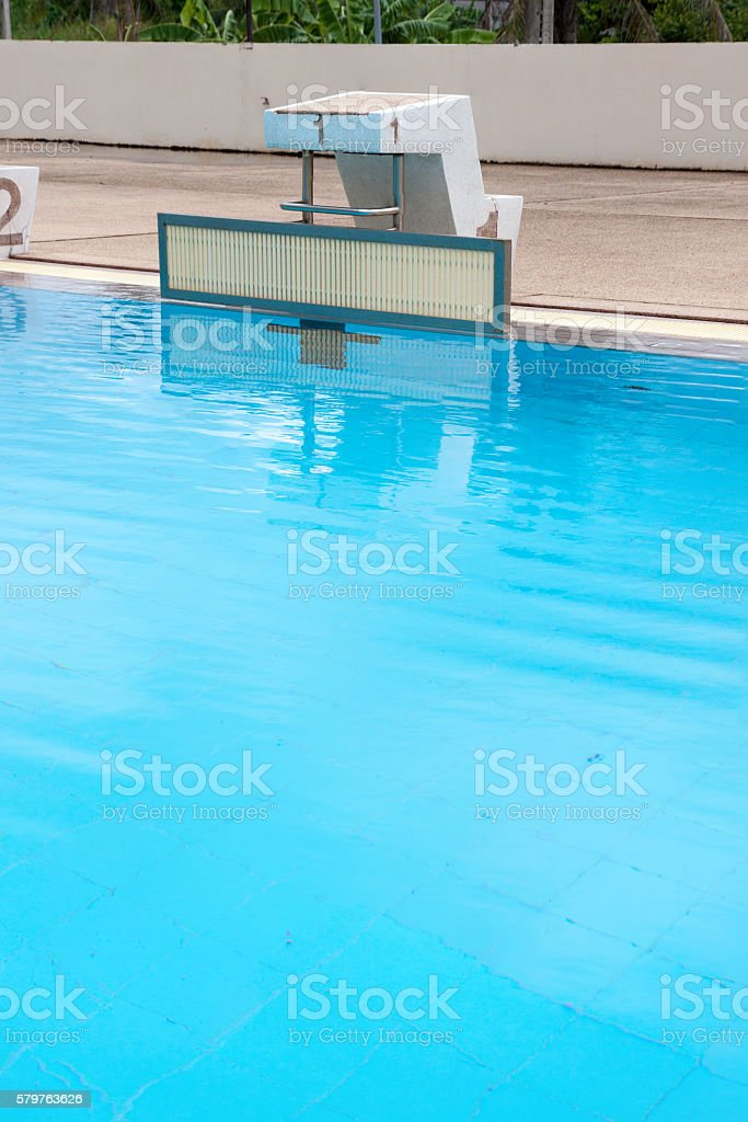 blue water wave in swimming pool reflects with sunlight , blue tile...