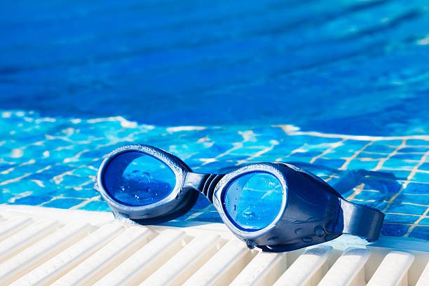 Swimming pool goggles on the poolside stock photo