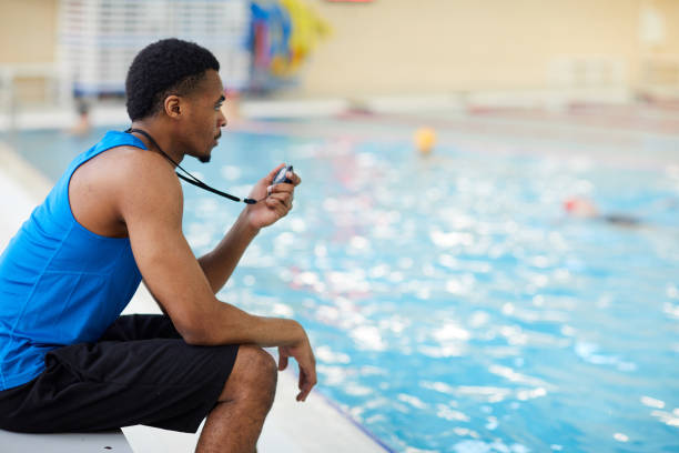 Swimming Pool Guard on Duty Side view portrait of handsome African-American fitness coach working in swimming pool, copy space lifeguard stock pictures, royalty-free photos & images