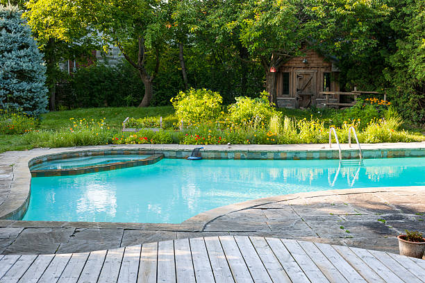 Swimming pool in backyard Backyard with outdoor inground residential swimming pool, garden, deck and stone patio backyard pool stock pictures, royalty-free photos & images