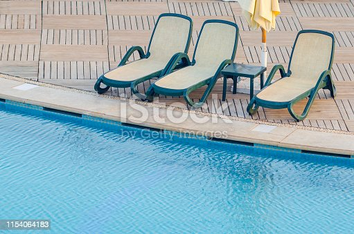 Swimming pool near the hotel with sun lounger and umbrella.
