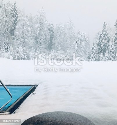 Swimming pool outdoor edge and snow covered winter wonder land