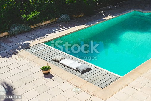 Swimming pool with clean turquoise water in it. Narrow wooden deck for sunbathing next to the pool.
