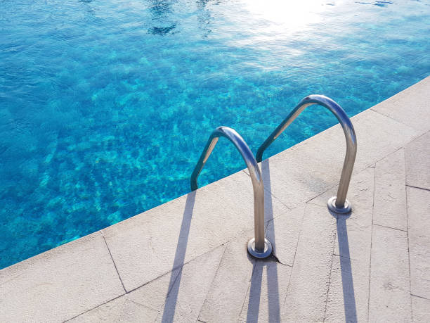 Swimming pool Ladder of the swimming pool cast a shadow swimming pool stock pictures, royalty-free photos & images