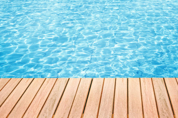 Swimming pool Abstract design of swimming pool water and wooden desk with space for text poolside stock pictures, royalty-free photos & images