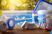 Swimming pool service and equipment with chemical cleaning products and tools on wood table and pool background. Horizontal composition. Front view