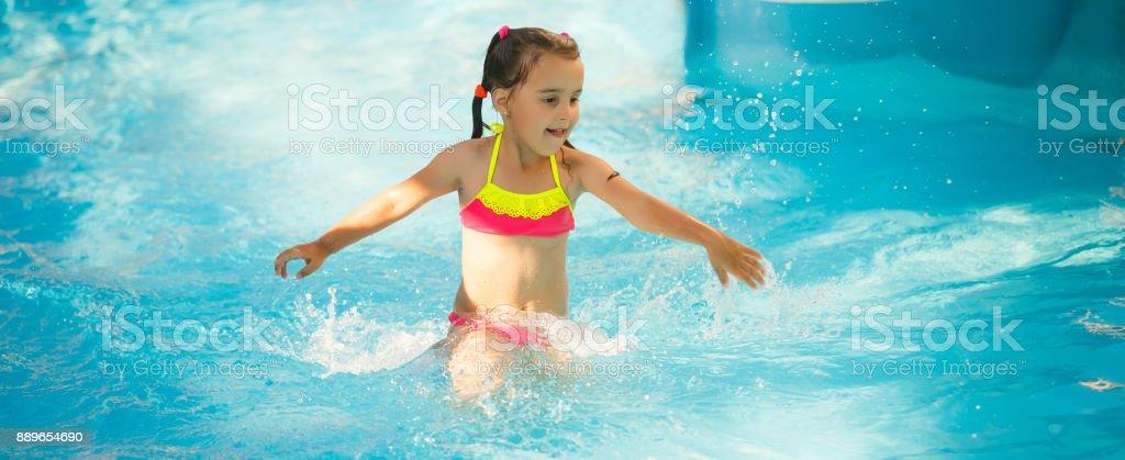 Swimming pool slides for children on water slide at aquapark . Summer kid holiday outdoor. Little girl in aqua park. stock photo