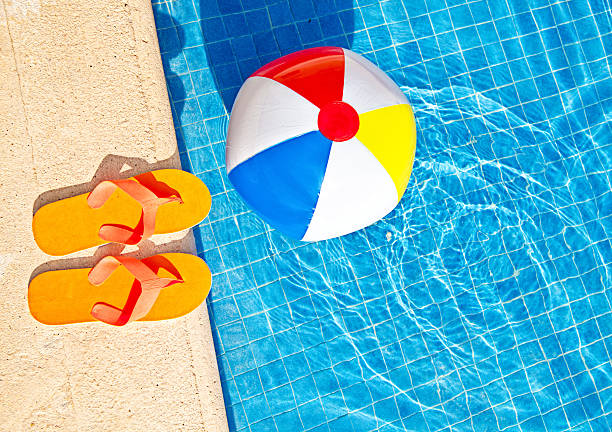 swimming pool summer fun with floating beach ball, flip flops - beach ball stock photos and pictures