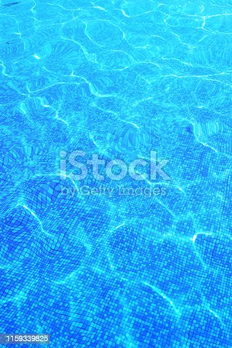 Swimming pool water background. Summer backdrop with blue shiny water with sun highlights in the pool. Mobile wallpaper. Instagram mobile story or stories size
