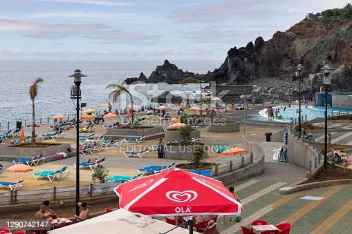 Funchal at Madeira, Portugal - July 31, 2014: Swimming pool with relaxing people at Atlantic coast of Madeira