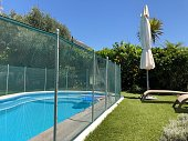 Home swimming pool in garden with safety fence