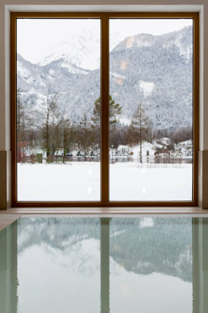 swimming pool with snow covered mountain lake view - hotel alpenblick stock-fotos und bilder