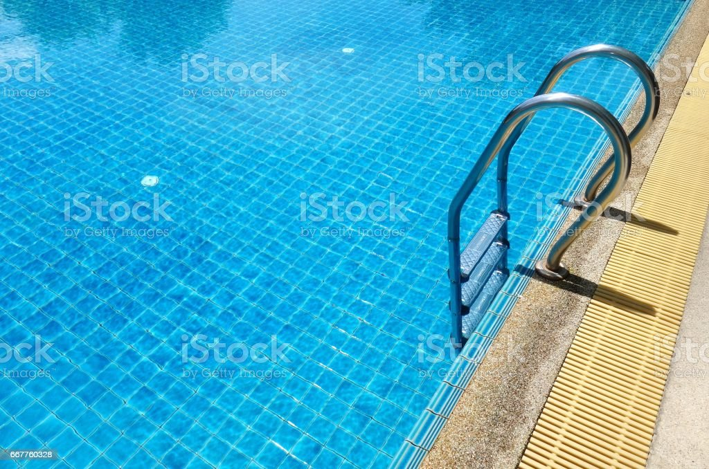 Swimming pool with stair and blue relaxing water stock photo