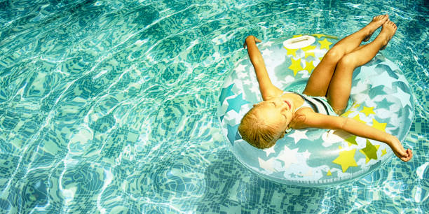 Swimming, summer vacation, Little girl on the swimming pool stock photo