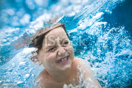 Close up of young boy swimming underwater. Bubbles are all around him.