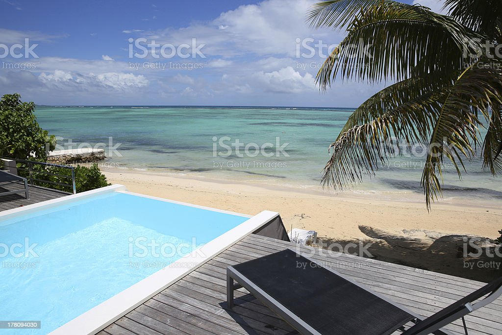 Swimming-pool with deck chair in front of the sea royalty-free stock photo