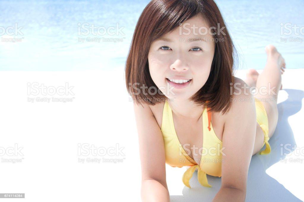 泳裝婦女躺在池邊 免版稅 stock photo