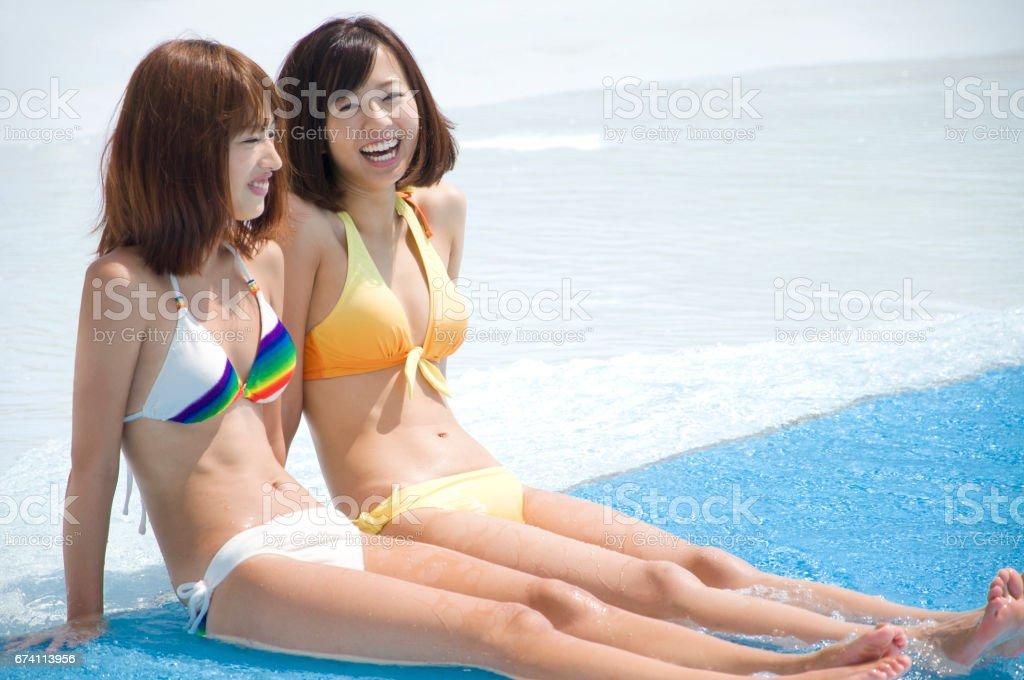 2 泳裝婦女坐在游泳池旁 免版稅 stock photo
