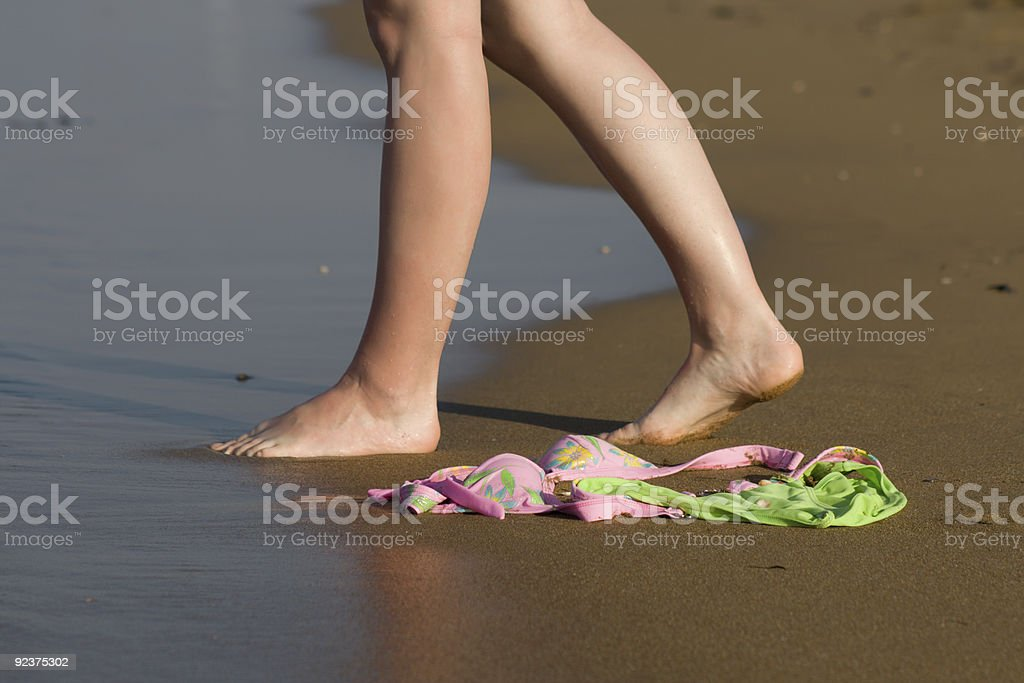 Swimwear on beach and woman walking to the sea royalty-free stock photo