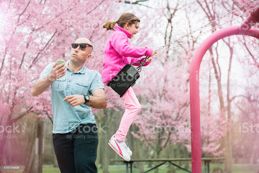 Swing Accident in the Park Parent gets hit by his daughter on the swing while watching smart phone. 2015 Stock Photo