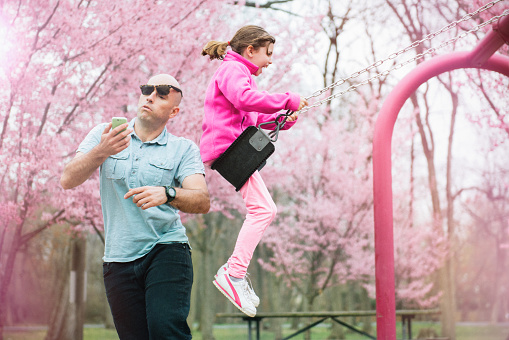 Parent gets hit by his daughter on the swing while watching smart phone.