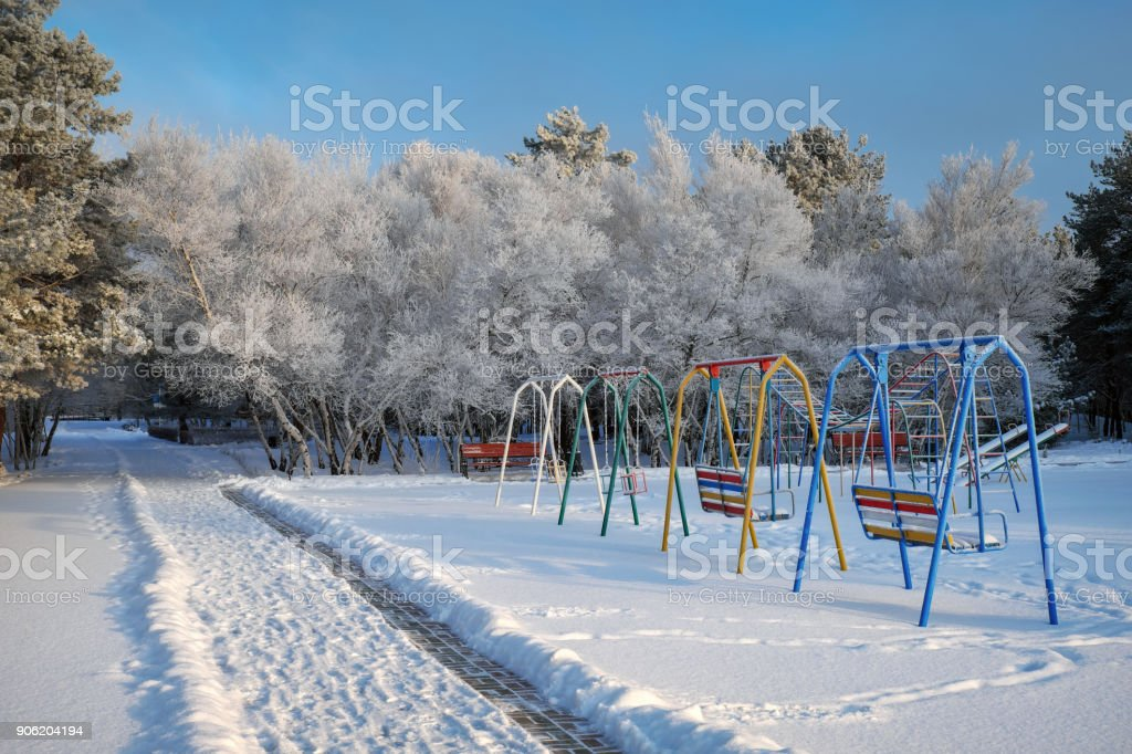 Swing at the playground covered with snow in winter time. Trees covered with hoarfrost. Road in the park stock photo